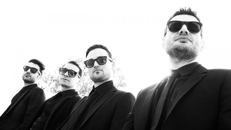 Foto in bianco e nero dei Matinée vestiti in giacca e cravatta e occhiali da sole