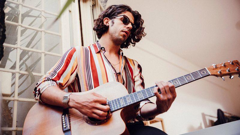 """Daniele Barsanti suona la chitarra in una foto promozionale per """"Le Commesse"""""""